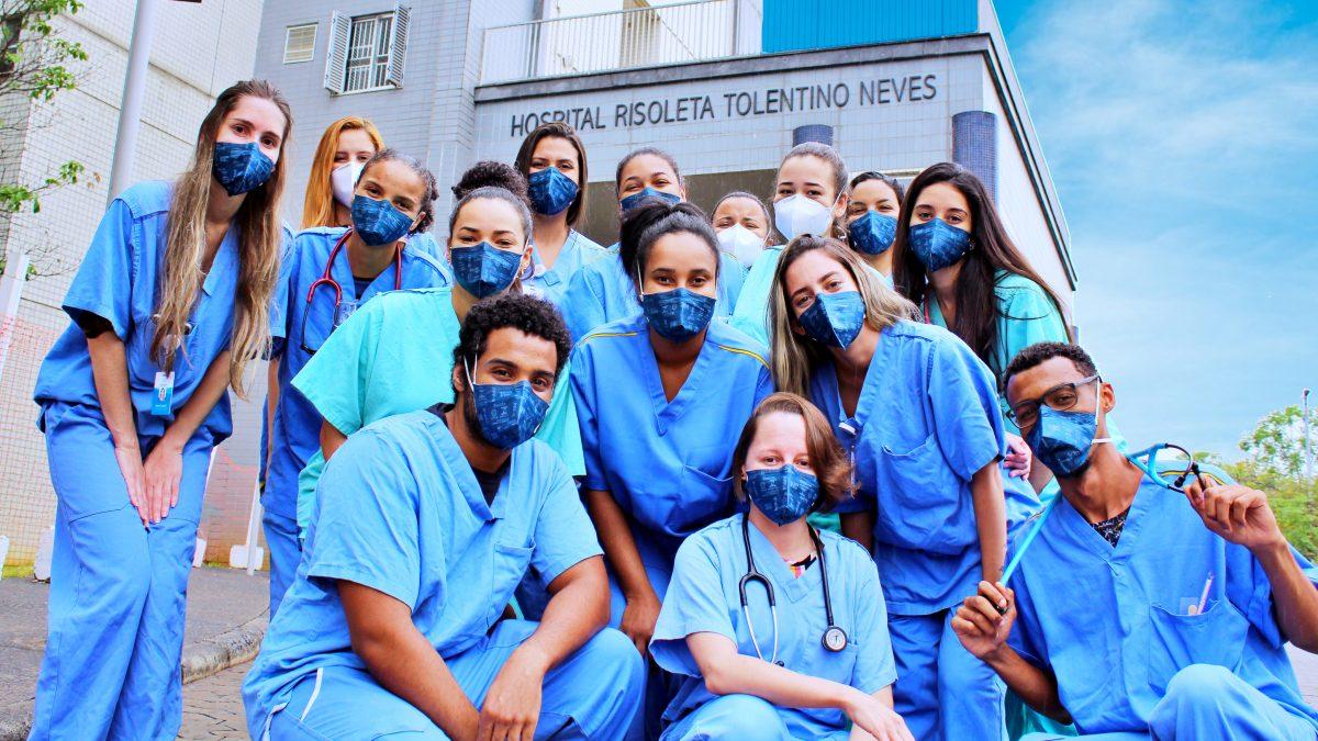 Um grupo de médicos usando máscara na frente do Hospital Risoleta Tolentino Neves