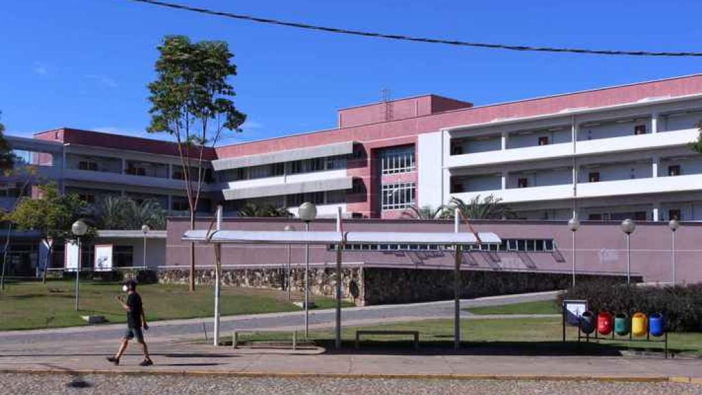 UFMG retoma atividades administrativas presenciais com ocupação máxima de 40%. A imagem mostra o prédio da FACE da UFMG. Um homem, usando uma máscara, caminha próximo ao ponto de ônibus em frente ao prédio.